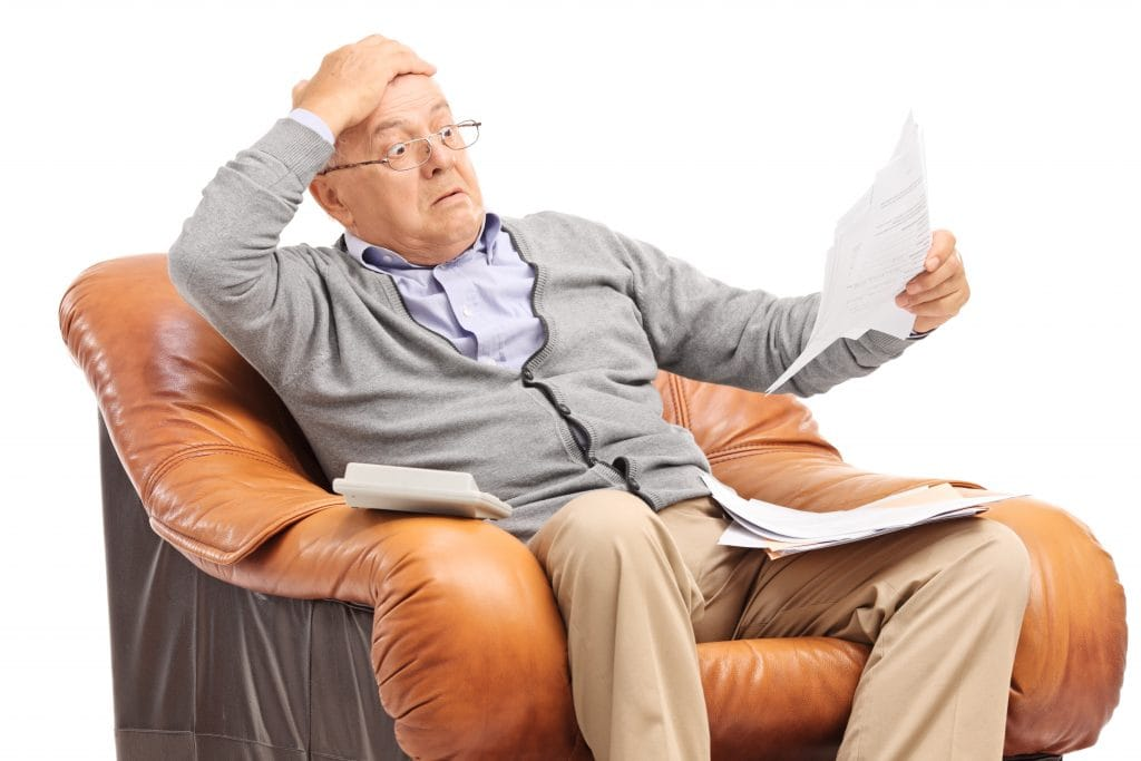 A man in in easy chair recoiling in response to paperwork unpleasant surprise