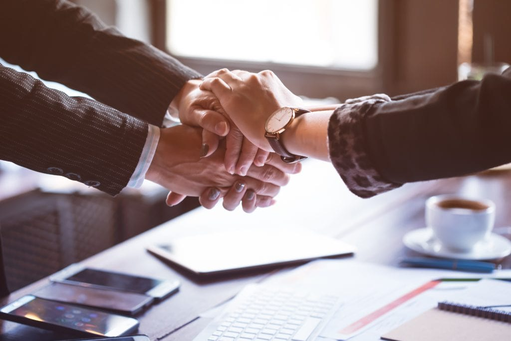 Settling a Trust; Picture shows arms of two persons shaking hands, representing settling the outstanding trust issues